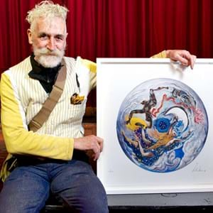 John Byrne posing with a replica of his design in a white frame