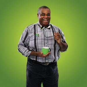 Clive Rowe dressed as Badger, holding a green cup of tea and smiling