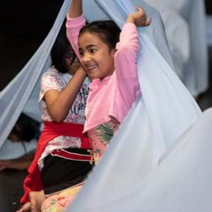 An Indian young girl dancing with some fabrics