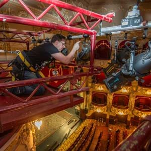 A member of the technical team on the light rig fixing a light at the King's Theatre